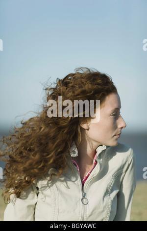 Junge Frau, die wegsehen, Haare im Wind wehen - Stockfoto
