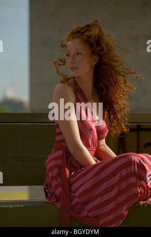 Junge Frau sitzt im Freien, Kleid, Haare im Wind wehen - Stockfoto