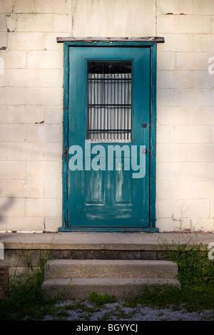 Eine einfache Türkis bemalte Holztür mit einem vergitterten Fenster. - Stockfoto