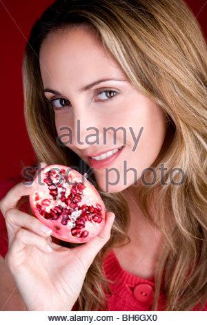 Eine Mitte erwachsenen Frau hält eine halbe einen Granatapfel - Stockfoto