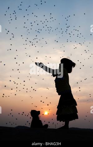 Silhouette eines indischen Mädchens Fang Sternschnuppen bei Sonnenuntergang. Indien - Stockfoto