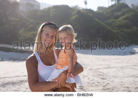 Mutter mit Babymädchen (12-15 Monate), am Strand, Lächeln, Porträt - Stockfoto