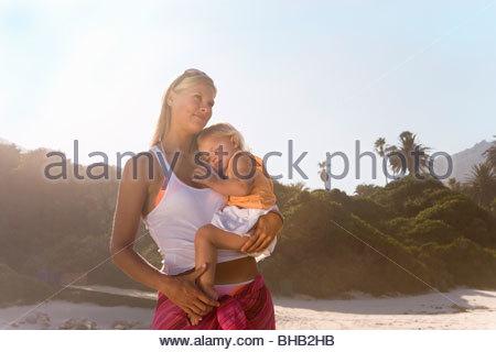 Mutter mit Babymädchen (12-15 Monate), niedrigen Winkel Ansicht (Lens Flare) am Strand - Stockfoto