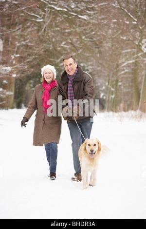 Älteres paar Walking Hund durch den verschneiten Wald - Stockfoto