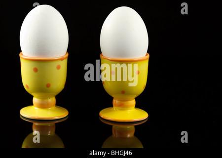 Hühnereier in punktierten Eierbecher auf reflektierenden schwarzen Hintergrund - Stockfoto