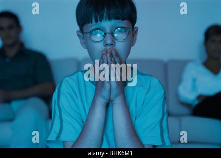 Junge vor dem Fernseher mit den Händen umklammert über Mund - Stockfoto