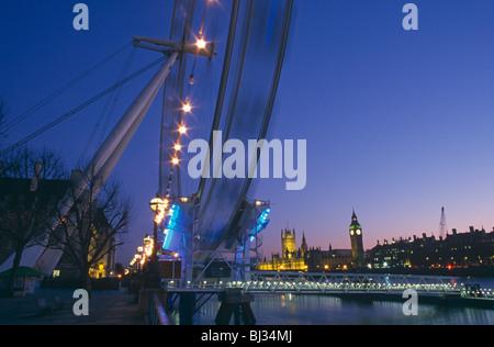 Je-Dreh London Eye ist über die Themse mit dem Palace of Westminster und dem Parlament über gesehen. - Stockfoto