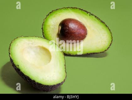 Hass Avocado Sorte Birne in Scheiben geschnitten in zwei Hälften auf einem grünen Hintergrund. - Stockfoto