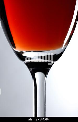 Weinglas mit roten Wein Nahaufnahme künstlerischen Stillleben über grauen Hintergrund vertikale Ausrichtung - Stockfoto