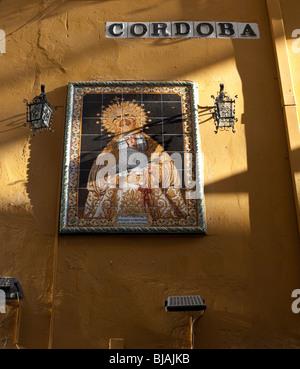 Streetsign buchstabieren Cordoba und gekachelte Bild des religiösen Symbols auf gelbe Wand in Spanien - Stockfoto