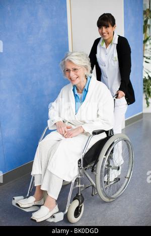Alte Frau in einem Rollstuhl und Krankenschwester - Stockfoto