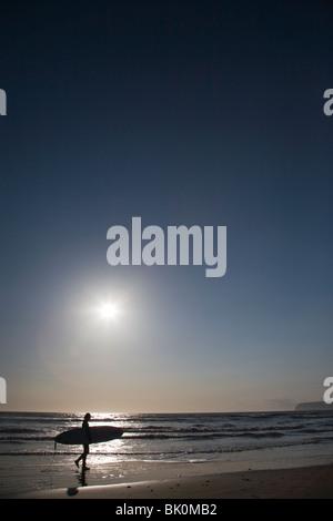 Junge Frau Surfer zu Fuß am Strand mit Surfbrett - Stockfoto