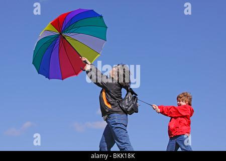 kleiner Junge hält sich an seine Mutter, die vom Wind weggeblasen wird ist - Stockfoto