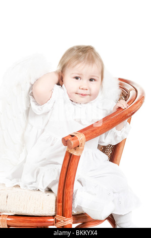 Kind sitzt auf dem Stuhl. Studio gedreht. Isoliert auf weißem Hintergrund. In Engelsflügel - Stockfoto