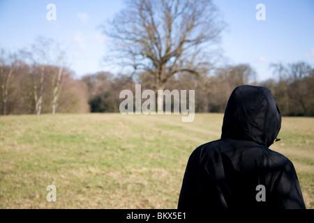 Rückansicht eines Mannes mit einem Kapuzen-Mantel in einem Park zu Fuß - Stockfoto