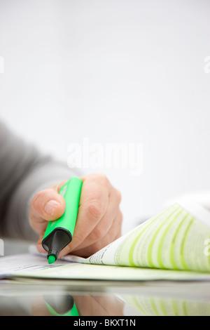 Nahaufnahme einer Frau Hand hält ein grüner Textmarker über ein Dokument in Papierform - Stockfoto