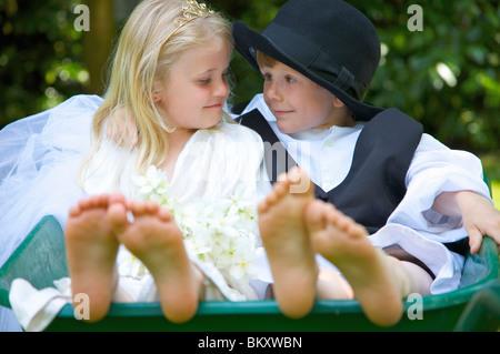 Junge und ein Mädchen tragen Braut und Bräutigam Kostüme sitzen in einer Schubkarre sahen einander - Stockfoto