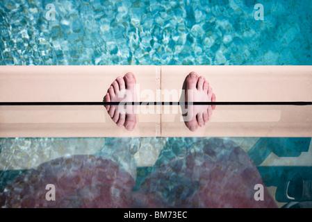 jemandes Füße am Rande eines Swimmingpools gegen Glas mit einer Reflexion Twin Füße - Stockfoto
