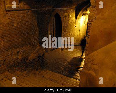 Person, die nachts in dunklen Gasse in Rom Italien - Stockfoto