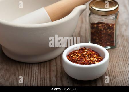 Zerkleinerte Chilischoten In einem weißen Teller mit einem Mörser und Stößel und Spice Einmachglas, auf einem hölzernen - Stockfoto