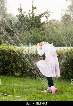 Mädchen spielen mit Rasen-Sprenger - Stockfoto