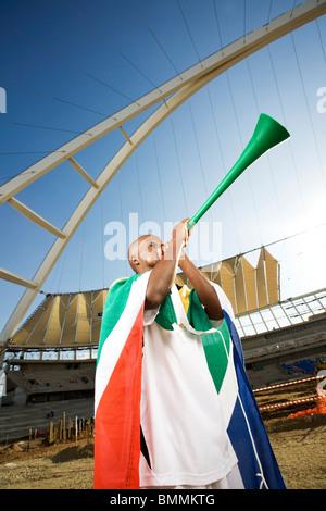 Fußballspieler mit südafrikanischen Flagge weht Vuvuzela, Moses Mabhida Stadium, Durban, Provinz Kwazulu-Natal, - Stockfoto