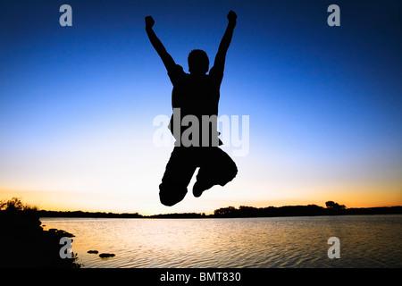 Willmar, Minnesota, Vereinigte Staaten von Amerika; Silhouette einer Person In die Luft springen, indem Sie das - Stockfoto