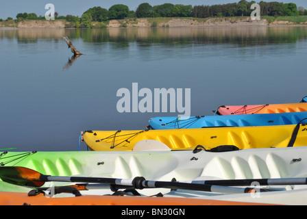 einige bunte Kajaks am Ufer eines Sees - Stockfoto