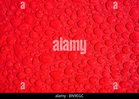 Nahaufnahme Makroaufnahme von Regentropfen auf einem roten Tisch - Stockfoto