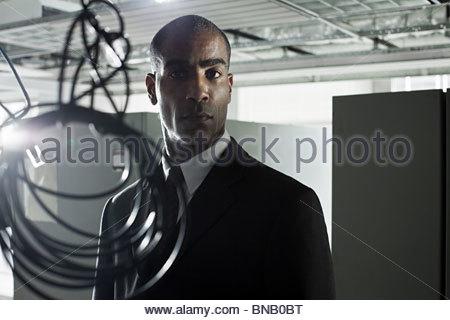 Geschäftsmann und Kabel in verlassenen Büro - Stockfoto