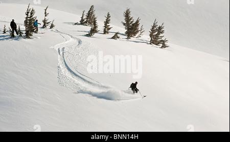 Ein Skifahrer und Snowboarder beobachten, wie ein Kerl Backcountry Skifahrer einen Abstieg in Turnagain Pass, Alaska - Stockfoto