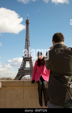 Rückansicht eines Mannes, ein Foto einer Frau vor dem Eiffelturm - Stockfoto