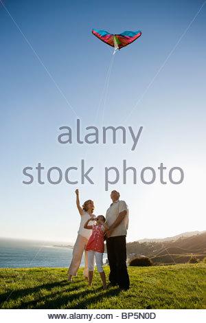 Großeltern und Enkeltochter fliegen Drachen auf dem Rasen mit Blick auf Meer - Stockfoto