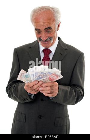 Senior sucht sehr glücklich hält eine Auswahl an britische Banknoten - Stockfoto