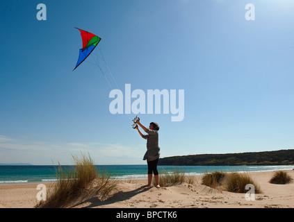Bolonia, Cádiz, Andalusien, Spanien; ein Mädchen einen Drachen am Strand von Costa De La Luz - Stockfoto