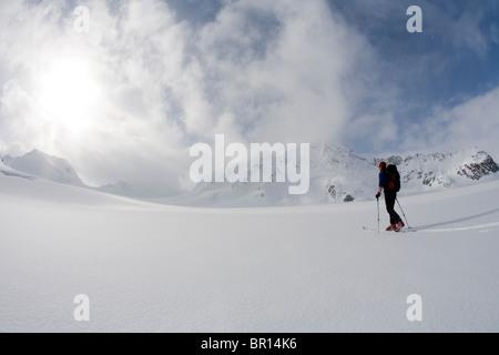 Backcountry Skifahrer kreuzt Gletscher unter Gewitterhimmel späten Tag. (Weitwinkel) - Stockfoto