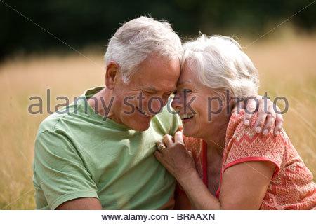 Ein älteres Paar, sitzen auf dem Rasen, lachen - Stockfoto