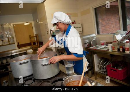 Schule Vorbereitung Abendessen kochen in einer Grundschule Küche, UK - Stockfoto