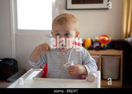 Junge 16 Monate alt einen messily Essen Joghurt essen. Hampshire, England. - Stockfoto