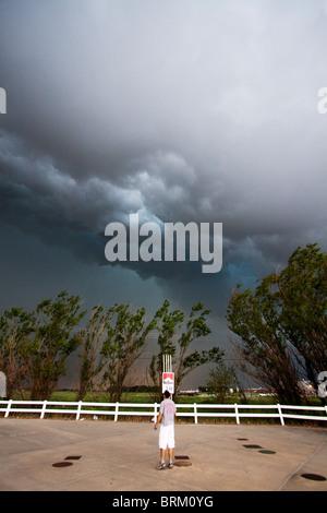Ein Mann steht auf einem Parkplatz und sieht eine Unwetterfront über ihn herfallen. 24. Mai 2010. - Stockfoto