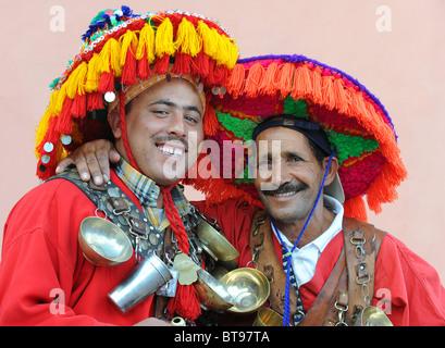 Zwei Wasser-Verkäufer posieren für Touristen in der Djema El Fna in Marrakesch. - Stockfoto