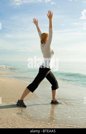 Frau beim Yoga am Strand - Stockfoto