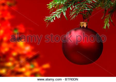 Rote Christbaumkugel hängend, mit textfreiraum auf der linken Seite. - Stockfoto