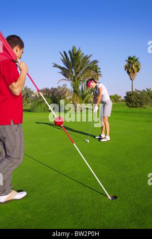 Frau Spieler putting Golf Golfball und Mann hält Flagge - Stockfoto