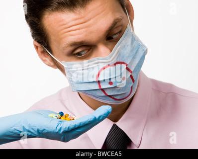 Foto der behandschuhten Hand, die Pillen und Mann mit Maske, die sie betrachten - Stockfoto