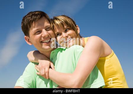 Foto von hübschen weiblichen umarmen glücklicher Mann gegen strahlend blauen Himmel - Stockfoto