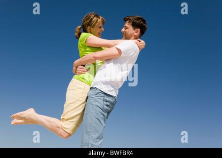 Foto des glücklichen Mann, hält seine Frau gegen strahlend blauen Himmel - Stockfoto