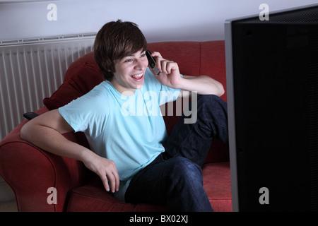 Junger Mann hält eine Telefon Lächeln auf den Lippen und vor dem Fernseher - Stockfoto