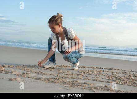Eine junge Frau schreiben In den Sand am Strand Los Lances In Costa De La Luz; Tarifa, Cádiz, Andalusien, Spanien - Stockfoto