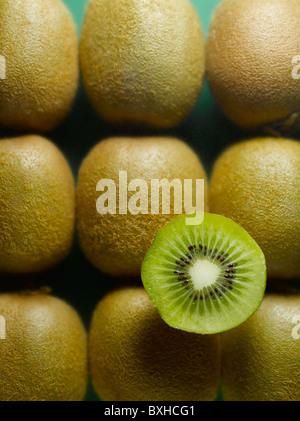 ganze Kiwis mit in Scheiben geschnittenen halben Kiwi auf grünem Hintergrund - Stockfoto